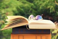 Geöffnetes Buch und Gläser, die auf Stapel Büchern auf natürlichem Hintergrund liegen Stockfoto