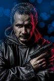Gefährlicher Geheimagent mit Gewehr- und Polizeinotbeleuchtungen Stockfotografie