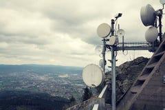 Gefiltertes Bild der Überwachungskamera mit Übermittlern und Antennen auf Telekommunikation ragen hoch lizenzfreie stockfotos