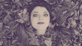 Gefiltreerd beeld met jonge dame in de bladeren Stock Afbeeldingen