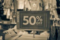 Gefiltreerd beeld 50 percenten van verkoopteken over kleren bij de opslag van de babykleding met klant het winkelen royalty-vrije stock fotografie