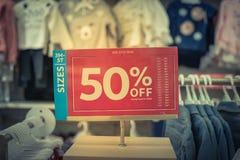 Gefiltreerd beeld 50 percenten van verkoopteken over kleren bij de opslag van de babykleding met klant het winkelen royalty-vrije stock foto's