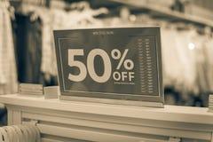 Gefiltreerd beeld 50 percenten van verkoopteken over kleren bij de opslag van de babykleding met klant het winkelen royalty-vrije stock afbeeldingen