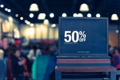 Gefiltreerd beeld 50 percenten van verkoopteken over kleren bij warenhuis met klant het winkelen stock afbeeldingen