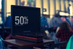 Gefiltreerd beeld 50 percenten van verkoopteken over kleren bij warenhuis met klant het winkelen stock foto