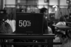 Gefiltreerd beeld 50 percenten van verkoopteken over kleren bij warenhuis met klant het winkelen royalty-vrije stock afbeeldingen