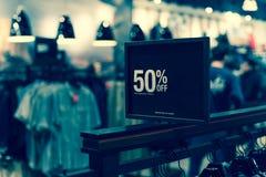 Gefiltreerd beeld 50 percenten van verkoopteken over kleren bij warenhuis met klant het winkelen stock afbeelding