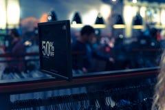 Gefiltreerd beeld 50 percenten van verkoopteken over kleren bij warenhuis met klant het winkelen royalty-vrije stock fotografie