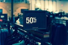 Gefiltreerd beeld 50 percenten van verkoopteken over kleren bij warenhuis met klant het winkelen royalty-vrije stock foto's