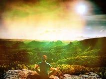 gefiltreerd De zitting van de mensenwandelaar op een rots in berg stock foto