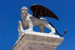 Geflügelter Löwe von Venedig stehend auf einer Spalte gegen den blauen Himmel Stockfotografie