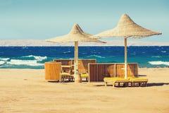 Geflochte Sonnenschirme auf dem einsamen Strand lizenzfreies stockfoto