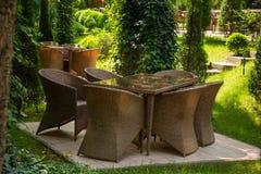 Geflochtene St?hle und Tabelle sind im Garten nahe B?umen lizenzfreie stockbilder