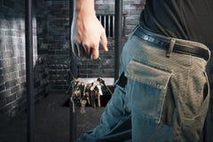 Gefängniswärter mit Tasten gehend außerhalb der Zelle Stockfotografie