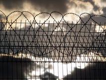 Gefängniszaun mit Stacheldraht Stockfotografie