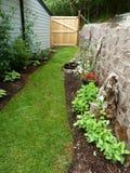 Gefochten im Garten mit Steinblockwand und -tor im Spätsommer Stockbild