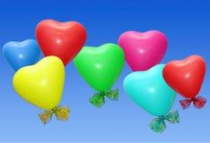 Geformte Ballone des bunten Herzens im Himmel Stockfotos