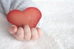 Geformte Karte des Herzens in der Babyhand Lizenzfreie Stockfotos