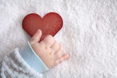 Geformte Karte des Herzens in der Babyhand Stockfotografie