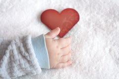 Geformte Karte des Herzens in der Babyhand Stockbilder