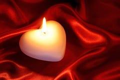 Geformte Kerze des Herzens auf roter Seide Stockfoto