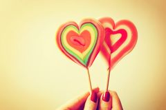 Geformte Lutscher des bunten Herzens in der Frauenhand stockbild