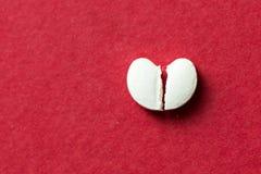Geformte Pille des Herzens geknackt zur Hälfte Stockfoto
