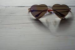 Geformte Regenbogensonnenbrille des Herzens auf hölzerner Beschaffenheit Stockfotos