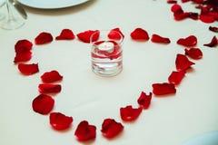 Geformte rosafarbene Blumenblätter eines Herzens Die Kerze auf dem Wasser innerhalb des Glases Romantische Dekoration Valentinsta Stockbild