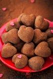 Geformte Schokoladentrüffeln des Herzens auf roter Platte Lizenzfreie Stockfotografie