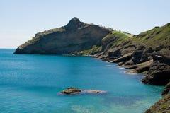 Geformter Berg des Krokodils im blauen Meer Stockfoto
