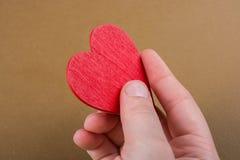 Geformter Gegenstand des rote Farbherzens in der Hand lizenzfreies stockbild