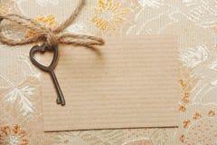 Geformter Schlüssel des Herzens auf einer Papierkarte stockfotografie