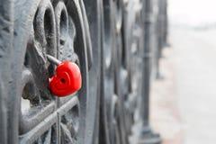 Geformter Verschluss des roten Herzens auf grauer Brücke Zu küssen Mann und Frau ungefähr lizenzfreie stockbilder
