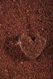 Geformtes Glas des Herzens mit zerriebener dunkler Schokolade lizenzfreie stockfotos