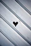 Geformtes Loch des Herzens im hölzernen Fensterladen stockfoto