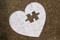 Geformtes Puzzlespiel des weißen Herzens auf goldenem glänzendem Hintergrund stockfotografie