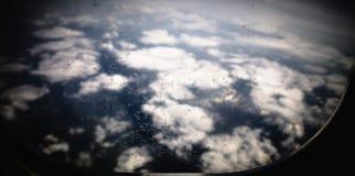 Gefrieren Sie Blumen auf Flugzeugfenster, mit Bergen und Wolken im Hintergrund Stockbilder