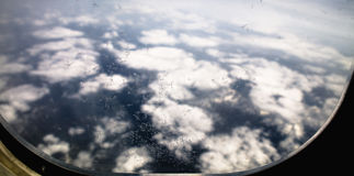Gefrieren Sie Blumen auf Flugzeugfenster, mit Bergen und Wolken im Hintergrund Lizenzfreies Stockfoto