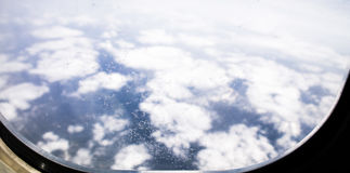 Gefrieren Sie Blumen auf Flugzeugfenster, mit Bergen und Wolken im Hintergrund Stockfotografie