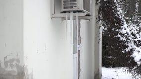 Gefrieren Sie den Stapel, der unter Wärmepumpesystem auf Hausmauer im Winter eingefroren wird Runde metallische Knöpfe 4K stock video footage