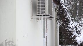 Gefrieren Sie den Stapel, der unter Wärmepumpesystem auf Hausmauer im Winter eingefroren wird Summen Sie innen laut 4K stock video