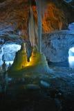 Gefrieren Sie die Stalagmite und Stalaktiten, die durch Kerzen innerhalb des Marmorbergwerkes belichtet werden Stockfotografie