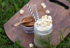 Gefrieren Sie Kakao mit dem Zimt und Schlagsahne, die mit Karamellpopcorn geschmückt werden Lizenzfreies Stockbild