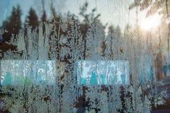 Gefrieren Sie Muster auf Fenstern mit Reflexion des Sonnenuntergangs in Wald gefrorenen Schneeflocken, Kristall des Eises Stockbild