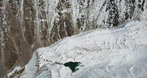 Gefrieren Sie See in der Schlucht unter den Felsen und dem Schnee Schießen von einem Brummen stock footage
