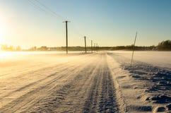 Gefrieren Sie Straße auf einem gefrorenen Gebiet auf einem dunstigen winterlichen Morgen Stockbilder