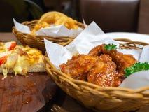 Gefrituurde kip in een mand met peterselie en zeevruchtenpizzabovenste laagje met Krab, garnalen en ham op een houten dienblad en Stock Afbeeldingen