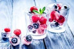 Gefrorene Beeren im Glas für Cocktail auf Holztischhintergrund Lizenzfreie Stockfotos