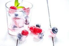 Gefrorene Beeren im Glas für Cocktail auf Holztischhintergrund Lizenzfreies Stockfoto